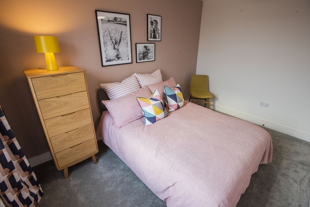 A colourful and modern double bedroom at Caerlee Mill