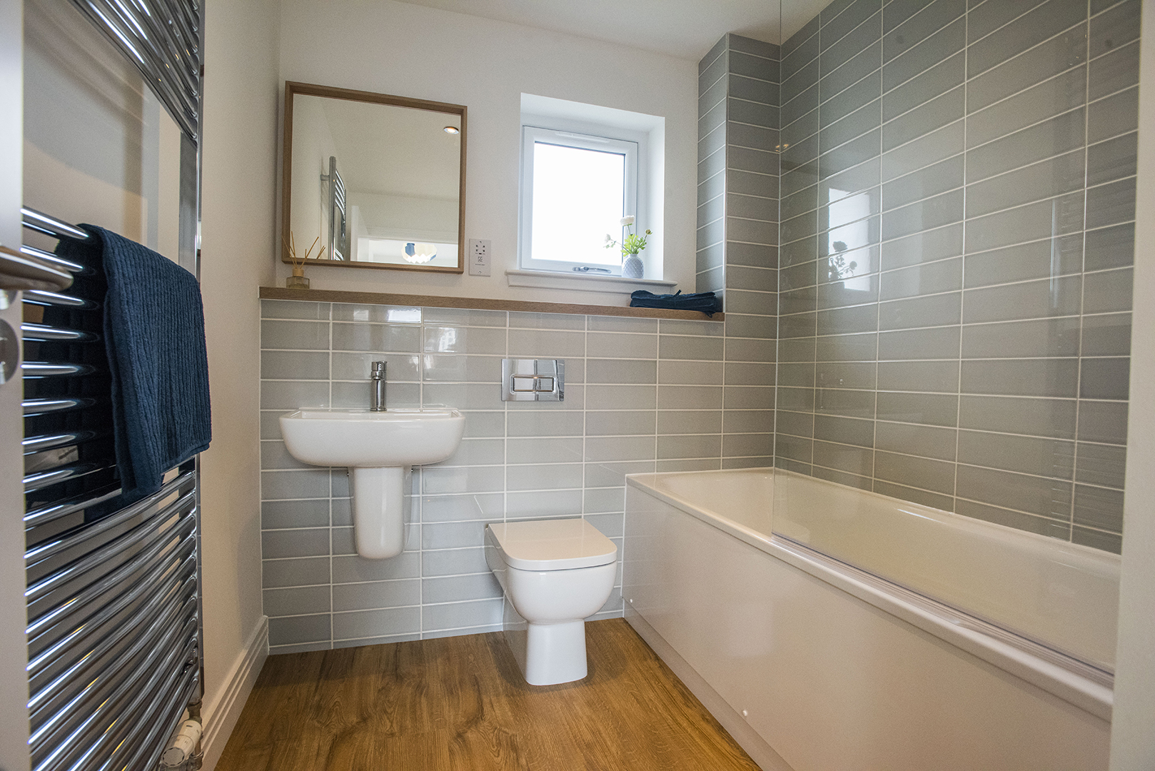 A bathroom with toilet, bath, sink and towel warmer