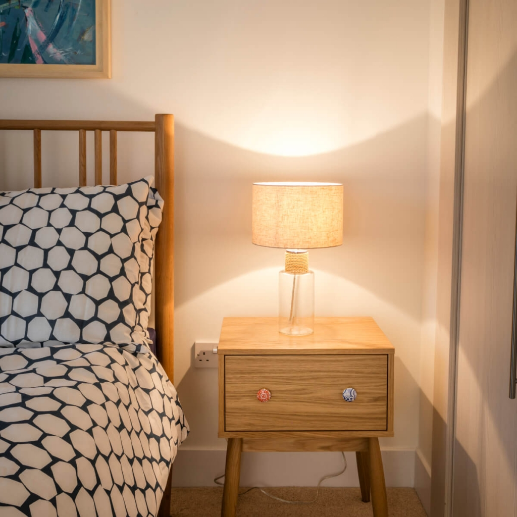 A warm feeling photo of a bedside lamp and cosy bed